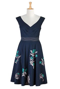 Our cotton poplin dress is embellished with fal florals at the full skirt while chevron pleats at the bodice add just the right fit for our retro-inspired silhouette.