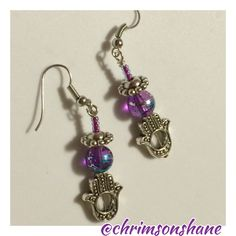 Pretty Purple Hamsa Earrings Pretty Hamsa earrings features blue-streaked purple glass beads and iridescent purple seed beads. Hamsa charm is silver tone.All of my handcrafted earrings are one-of-a-kind. Have a nickel allergy? Let me know and I'll be glad to change out the hooks on any of my handcrafted earrings so they are wearable for your sensitive ears.  Top-Rated Seller Fast Shipper Top 10% Seller Discount on Bundles Free Gift For All Orders $20 & up No Paypal No Trades Lucky Nut…