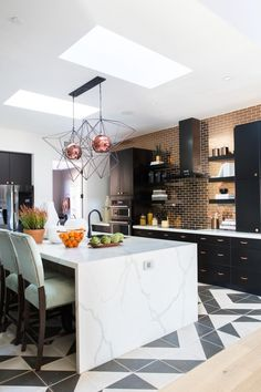 A graphic black and white tile floor, a waterfall quartz topped island and a stunning copper subway tile backsplash give this open kitchen serious style, while smart technology helps make cooking and daily activities easier. >> http://www.hgtv.com/design/hgtv-smart-home/2017/kitchen-pictures-from-hgtv-smart-home-2017-pictures?soc=pinterest