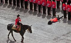 ImgurA British foot guard passes out as Queen Elizabeth II rides past during the colour parade in June, 1970. Imgur