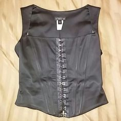 Black Bebe Corset Solid black ( acetate blend) Bebe Corset with silver eyelet hook closure down the front. Amazingly bust enhancing and slimming! Wardrobe must! Gently worn great condition. Vintage Tops Crop Tops