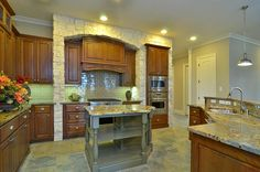 Love this kitchen...mixing traditional cabinets with a gray island...formal yet welcoming.