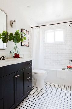 Black and White Bathroom with subway tiles, dark painted cabinets with white countertops, interesting tile detail around windows.