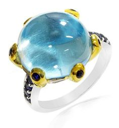Featuring a beautiful Cabochon cut Blue Topaz which sits majestically atop of a Gold plated prongs, this ring offers a gorgeous combination of fashion and style. The ring is also studded with 14 smaller Blue Sapphires on both the band and the prongs.