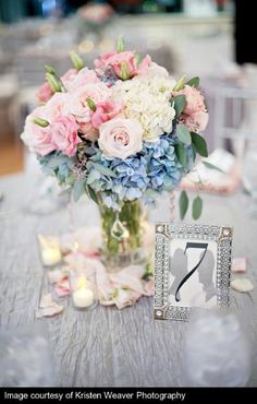 Centerpiece this size and shape, but with blue and purple flowers with candles around the bottom.
