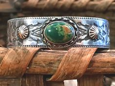 """Fred Harvey 1920s Navajo tourist bracelet. Sterling silver set with natural green Hachita Mine turquoise. Nice fluted buttons. Interior, 5 3/8"""" circumference, with 1 1/4""""L opening. Weight, 20.6 grams."""