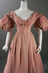 "ball or dinner gown, circa mid-1830s, exhibits the popular fashion of the period with its wide neckline, small waist, bell shaped skirt and full ""beret"" sleeves, a variation of the gigot sleeve.  It is made of rose silk bengaline."