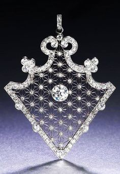 Diamond Pendant, ca. 1910...the articulated triangular openwork plaque, centrally-set with a collet-set old brilliant-cut diamond, within star-shaped latticework accented by single-cut diamonds, to a scrolled border millegrain-set throughout with cushion-shaped and old brilliant-cut diamonds, detachable brooch frame, via Bonhams.