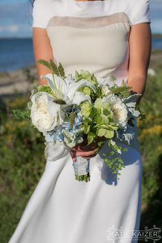The bride shows off her bouquet at a sleek Nantucket wedding.  Photo by: http://katiekaizerphotography.com/ Flowers by: http://flowersonchesnut.com/