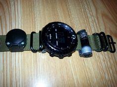 tiny flashlight holder on watch band.  Possibly Streamlight flashlight