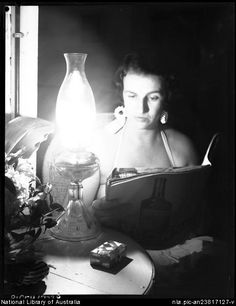 Woman reading by coal oil lamp before everyone had electricity.