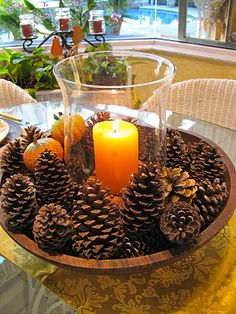 wooden bowl, pine cones and mini pumpkins, glass hurricane, and a candle. simple and beautiful