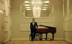 Kyle DeSantis stands by a piano in the Crystal Room at Drury Lane Oakbrook.