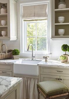 French country kitchen features light taupe cabinets paired with white marble countertops and a white subway tiled backsplash accented with white grout.