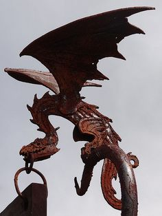 Here be dragons - One of two holding up a sign outside the Weta Cave in Wellington, New Zealand
