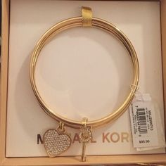 Micheal Kors bracelet set NWT. BRAND NEW! Still in box, with tags. Gold Michael Kors braclet set. Key and heart charms. Michael Kors Jewelry Bracelets