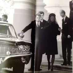 1963-11-25: Jackie, Bobby and Teddy arrive back at the White House after accompanying JFK's body from the Capitol. Chief of Protocol Angier Biddle Duke helps Jackie out of the limousine and shows her where to stand while waiting for the march to the cathedral to begin.