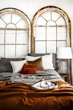Rustic bedroom with antique arched windows as an alternative headboard, glass jug finial table lamp and rich rust colored velvet bedding.