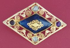 15C --- Gem-set & enamelled lozenge-shaped gold brooch --- seen on eBay, July 2014, seller nadinekrakov, item number 281024890996 --- The brooch-pin on the back is a later addition;  there are two flat pins under the brooch pin, suggesting that this may have originally been a dress or hat mount (could it even have been for men as well as women?).