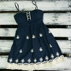 Navy dress with cream lace trim Adorable dress! Flowers are embroidered. Top has bra cups in it. No stains or tears. Worn once. Zips in back as well as a sash tie (pic 2). Spaghetti straps are not adjustable. Dresses Mini