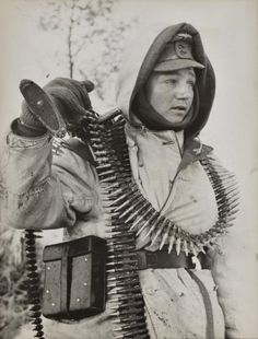 The face of war: festooned with ammunition belts this young grenadier, complete with machine gun and dressed in winter clothing, prepares to move off— Eastern Front, April 1943.