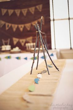 Teepees made out of twigs for table centerpieces, burlap runner with feather banner, little brave man party
