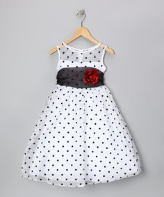 Fun and flouncy, this charming dress is perfect for playful little princesses. Classic polka dots that never go out of style are paired with a rose accent on the ebony sash.