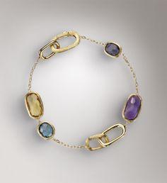 18K yellow gold bracelet, hand engraved with the time-honored Bulino technique. This jewel mounts cushion cut, irregular and faceted Yellow Quartz, London Topaz, African Amethyst and Iolite stones.