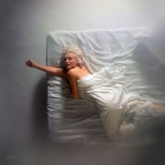 """1961. """"Marilyn Monroe posed on a bed under white sheets."""" Photo by Douglas Kirkland for the Look magazine assignment """"Four for Posterity."""""""