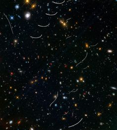 This Hubble photo of a random patch of sky is part of a survey called Frontier Fields. It contains thousands of galaxies, including massive yellowish ellipticals and majestic blue spirals. Much smaller, fragmentary blue galaxies are sprinkled throughout the field. The reddest objects are most likely the farthest galaxies. Asteroid trails appear as curved or S-shaped streaks. Of the 20 total asteroid sightings for this field, seven are unique objects. (Credits: NASA, ESA, STScI)