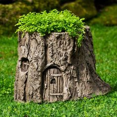 This charming hand-cast stone planter is shaped like a tree stump that comes complete with a little door and window on the side.