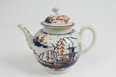 LOT 128  18th century Worcester porcelain teapot and cover with rare brick-red and blue 'Candle Fence Pavilion' pattern decoration - underglazed blue crescent mark to base, 19cm