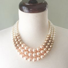 The Color Block Necklace features a classic silhouette with bold color blocking, making it perfect for the modern woman with timeless style. This necklace features luxurious Austrian crystal pearls in Ivory, Soft Gold, and Peach, arranged in a blocked motif. Pearls taper in graduated sizes, from 6mm to 12mm. The necklace fastens with a silver plated hook clasp. The shortest tier is about 18 inches long.  Your necklace is packaged in a signature crisp white Demoiselle jewelry box, perfect for…