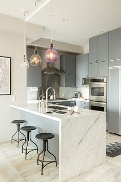 Beautiful carrara waterfall countertops for a modern kitchen style, with designed round chair, color lighting
