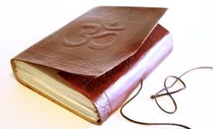 A Unique hand made recycled paper journal or sketch book from India. This piece has beautiful imprint of the mantra OM on the leather cover and patterns in the front and back of the book