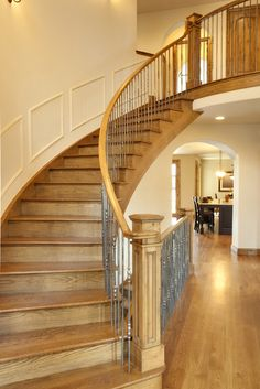 A wooden curved staircase with metal spindles lined with light wood handrail and newel post. It is fixed on a cream wall styled with wainscoting. Wooden Staircase Railing, Timber Stair, Wood Handrail, Wooden Stairs, Modern Staircase, Staircase Design, Staircase Ideas, Spiral Staircases, Metal Spindles