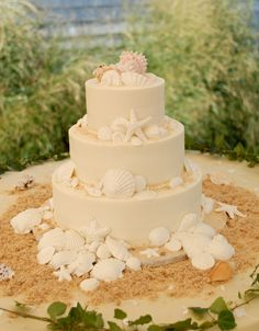 This buttercream with white chocolate wedding cake features sugar sand and shells. See more coastal cakes at http://dailycatch.coastalliving.com/2015/06/24/coastal-wedding-cakes-part-ii-cape-cod-edition/