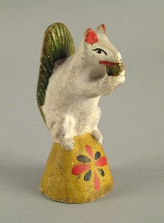 """Realized Price: $ 3978   Chalkware figure of a squirrel, 19th c., eating a nut atop a vibrant yellow base, 5"""" h. RICHARD MACHMER COLLECTION 2008"""