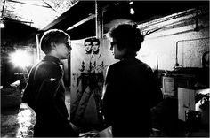 A photograph by Nat Finkelstein shows Bob Dylan visiting Andy Warhol at the Factory in 1966.