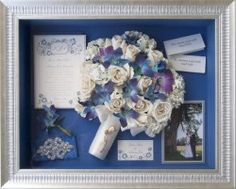 "This storybook creation includes the invitation layered above the envelope, garter, name cards from table, Grandmother's broach on white satin stem, and wedding picture with a framed border made from ""Silver Florentine"".  Forever Flowers Boca Raton FL. The 16x20 shadowbox is with the Silver Ribbed frame and Museum Glass.  Background is ""Flag Blue"".  Flowers are White Hydrangia, Vendella Roses, and Blue Dendrobium Orchids. Roses have supplied gems in the center of each bloom."