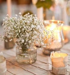 Baby's breath in apothecary jar illuminated by votives wrapped in vintage book pages.