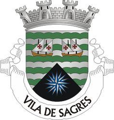 """Civic heraldry of Portugal - Brasões dos municípios Portugueses - Escudo de prata, cinco faixetas de verde, mantel de negro, carregado de uma rosa de ventos de prata e azul, acompanhado em chefe de duas caravelas de sua cor, vestidas de prata com a cruz da Ordem de Cristo nas velas, a da sinistra voltada. Coroa mural de prata de quatro torres. Listel branco com a legenda a negro, em maiúsculas, """" VILA DE SAGRES """".   The arms were officially granted on May 30, 1994."""