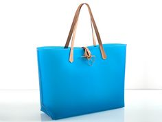 JESSICA VINYL BLUE HANDBAG Tote bag made of treated vinyl with neat leather details and strap. Item has been designed for rainy cities as well as trendy beach spots. Designer JT knows exactly what a sophisticated, delicate woman is craving for
