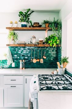 Forget kale – a kitchen like this is all you need for a healthy green fix. For a fresher take on emerald, a splash of deep sea green in a white kitchen makes for an inviting space. Again, texture is key here – the glossier and more imperfect the surface of your tile, the better. Try Mosaic Del Sur's Zelliege range for a similar crackle glazed tile. Add a rustic element with chunky reclaimed wood shelves and loads of greenery. #refinery29…