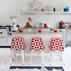 metal stools, slipcover, red, white, subway tile, open shelving, white cabinets, super adorable slipcovers for metal stools that look like little skirts!