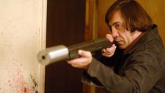 Anton Chigurh (Javier Bardem) holds a Remington Model 11-87 shotgun with a homemade supressor mounted on it.