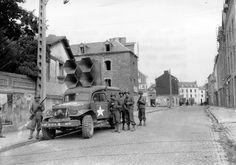 Dans le haut de la cote des Masses (actuellement rue Robert Schuman) à Paramé (actuellement Saint-Malo), des soldats US, dont certains sont armés, à côté de leur camion Dodge WC54 Ambulance, modifié avec un  equipment Public Adress  garé le long dun trottoir et équipé de hauts- parleurs.