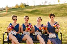 autumn bridesmaid in blue with bouquets of local orange, purple and pink dahlias, peach garden roses and white ranunculus.  And cute coordinated handbags!  www.redpoppyfloral.com