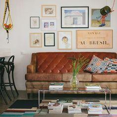 sala de estar linda com sofá de couro e quadros em tons terrosos...