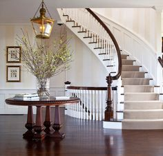 This otherwise conservative foyer loosens its tie with the large-scale and anti-arranged bouquet of budding branches. The delicate green and white blossoms might be lost in another setting, but they add a welcome touch of color here. Nantucket cottage designed by Jeannie Balsam LLC